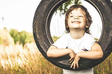 Kleiner Junge lächelt auf einer Reifenschaukel