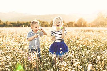 Zwei Kinder spielen auf einer Blumenwiese lachend mit Seifenblasen